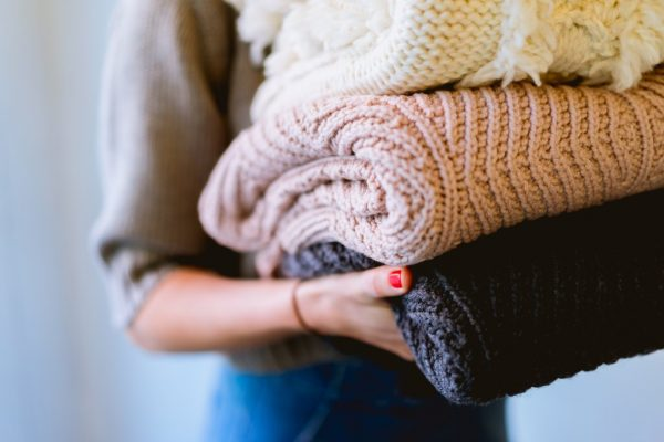 a woman carrying thick wool sweaters