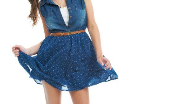 a woman in a navy blue dress touching her skirt