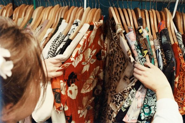 a woman looking through a cabinetof seasonal clothes