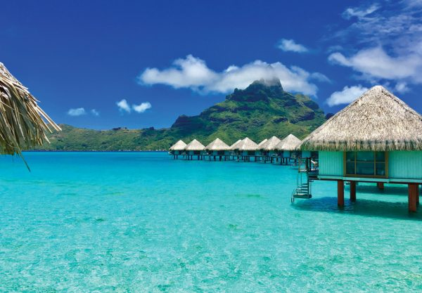 bungalows lined up in the crystal blue water in tahiti