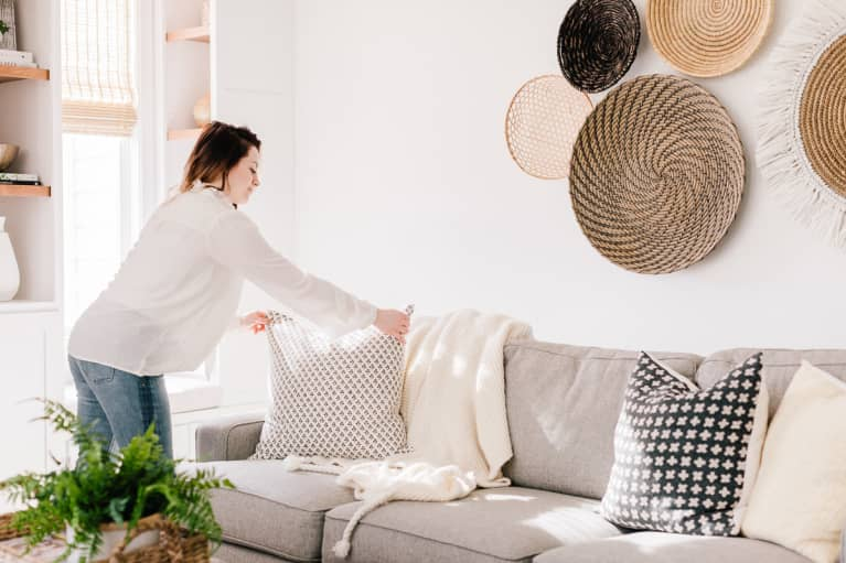 a woman arranging the throw pillows on a couch