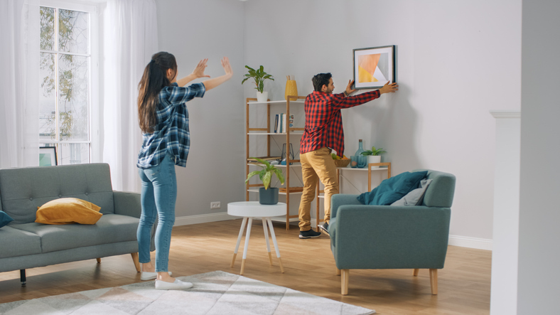 a young couple hanging a painting on their wall