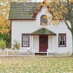 Small white home with autumn leaves