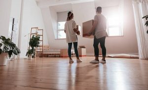 Couple standing in empty room with boxes
