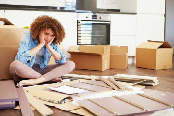 frustrated woman putting together self assembly furniture