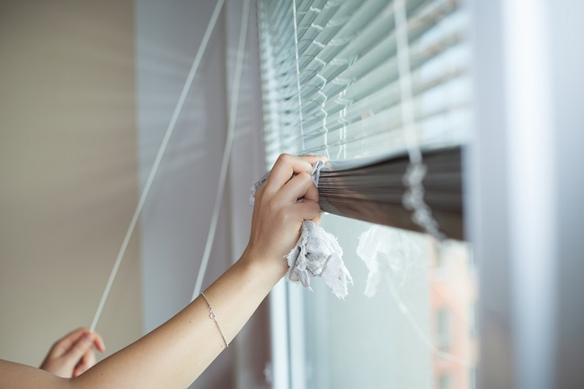 a woman manually putting up the blinds using her fingers
