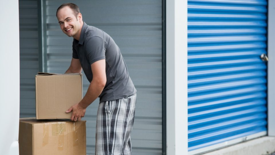 a man stacking boxes in his storage unit