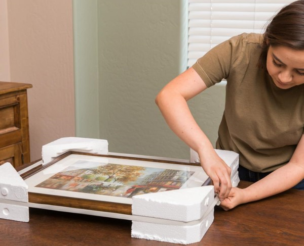 a woman carefully packing a framed painting