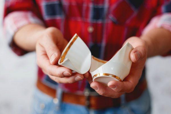 Man in plaid tartan shirt holds a broken white cup