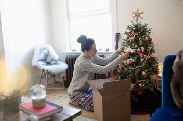 A woman decorating a christmas tree