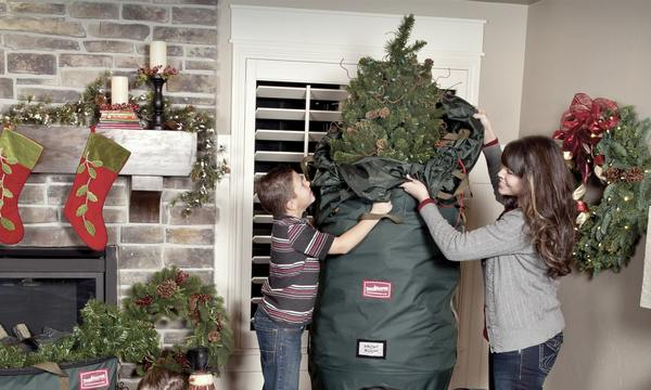 A mom and her son removing the christmas tree from its bag