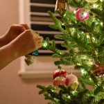 Person putting decoration on Christmas tree