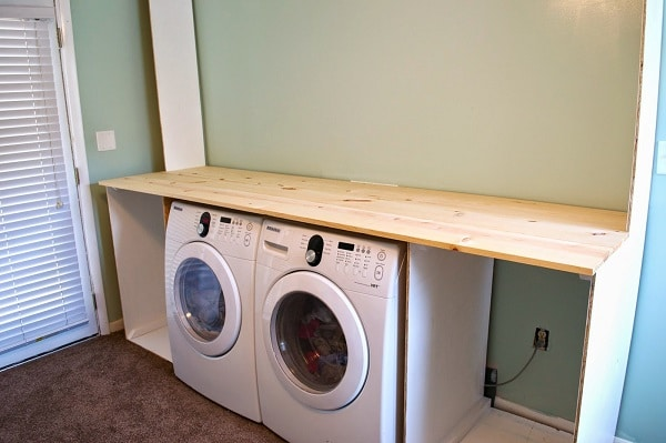 Two washers underneath a laundry countertop