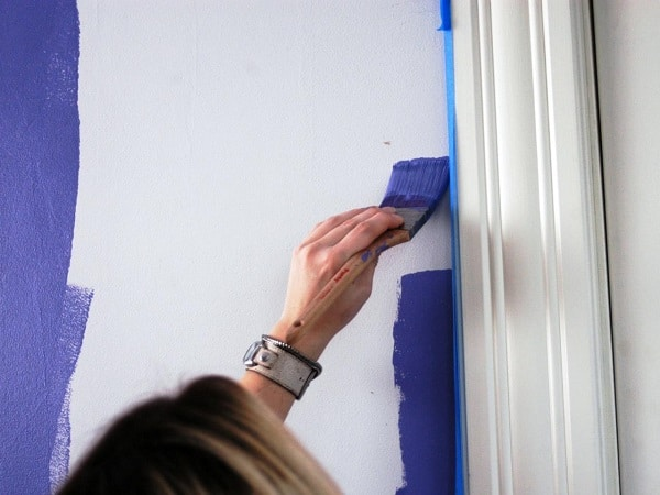 A woman painting the wall blue with a paintbrush